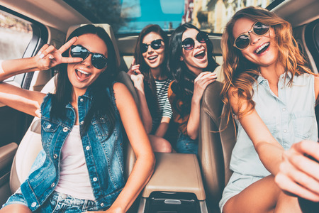 Just fun and road ahead. Four beautiful young cheerful women looking happy and playful while sitting in car Stock Photo