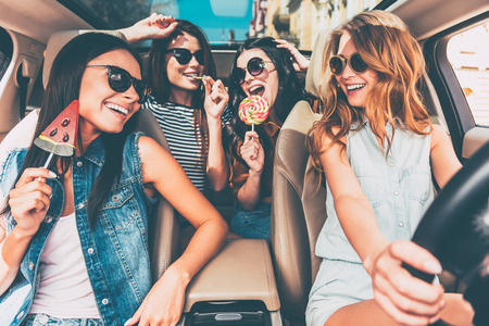 Great start of their journey. Four beautiful young cheerful women looking at each other with smile and holding lollipops while sitting in car