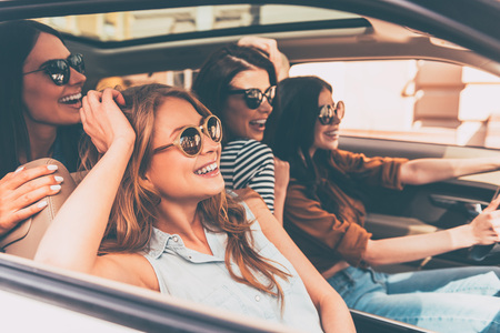 driving a car: On the road together. Side view of four beautiful young cheerful women looking away with smile while sitting in car Stock Photo