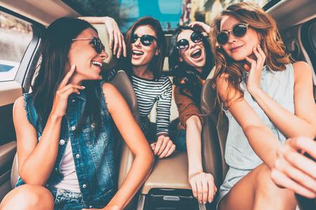 Genießen Straße Reise zusammen. Vier schöne junge fröhliche Frauen, die glücklich und spielerisch, während sitzen im Auto Standard-Bild