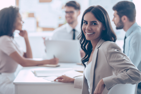 Feeling satisfied with her team. Beautiful cheerful woman looking at camera with smile while sitting at the office table with her coworkers