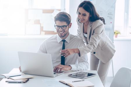 Ya tenemos grandes resultados! hermosa mujer joven que señala en la computadora portátil con una sonrisa y hablando de algo con su compañero de trabajo mientras está de pie en la oficina
