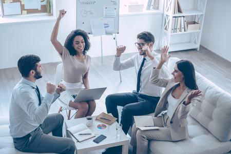 personas sentadas: Equipo de éxito. Vista superior de un grupo de cuatro jóvenes que gesticulan y parece feliz mientras está sentado en el sofá de la oficina
