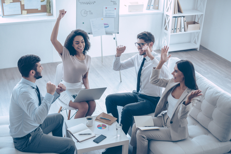 sitting people: Successful team. Top view of group of four young people gesturing and looking happy while sitting on the couch at office Stock Photo