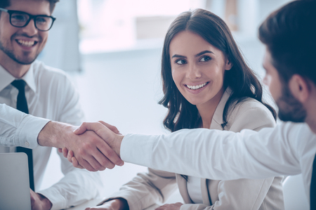 coworker: Business handshake. Close-up of two young man shaking hands with smile while sitting at office with their beautiful coworker