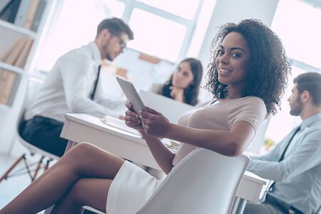 legs crossed at knee: Ready for brainstorming. Beautiful cheerful African woman holding digital tablet and looking at camera with smile while sitting at the office table with her coworkers Stock Photo