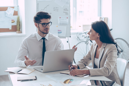 combining: Combining their expertise. Young handsome man in glasses gesturing and discussing something with his beautiful coworker while sitting at the office table Stock Photo