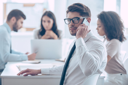 important phone call: Important business call. Handsome young man in glasses talking on mobile phone and looking at camera while sitting at the office table with his coworkers