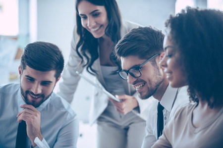young executive: Enjoying working together. Close-up part of group of four people looking down with smile while sitting at office
