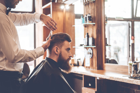 closeup view: Perfect cut. Close-up side view of young bearded man getting haircut by hairdresser at barbershop