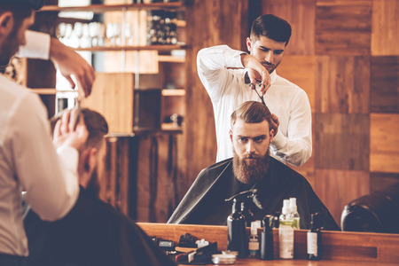 Haircut must be perfect. Young bearded man getting haircut by hairdresser while sitting in chair at barbershop in front of mirror