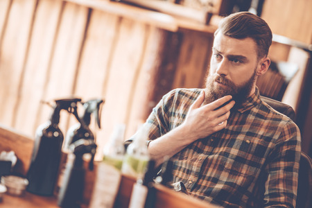 male hair: It is time for grooming. Handsome young bearded man looking at his reflection in the mirror and keeping hand on chin while sitting in chair at barbershop