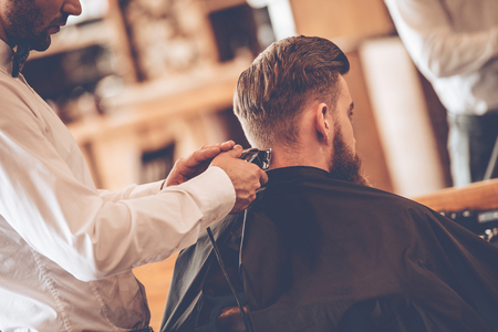 electric razor: Perfect  trim. Rear view close-up of young bearded man getting haircut by hairdresser with electric razor while sitting in chair at barbershop