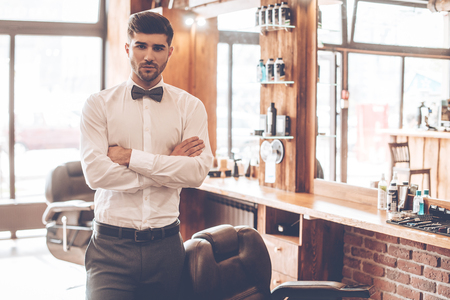 business service: Loving his job. Young handsome man looking at camera and keeping arms crossed while standing at barbershop Stock Photo