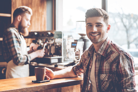 best coffee: Enjoying best coffee in town. Young handsome man looking at camera with smile while sitting at bar counter at cafe with barista at the background