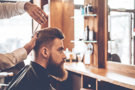 shop skill: Perfect cut from back to front. Close-up side view of young bearded man getting haircut by hairdresser at barbershop Stock Photo