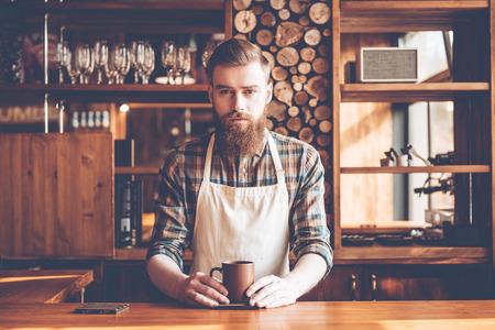 mandil: barista confianza. hombre barbudo joven en delantal que mira la cámara y la celebración de la taza de café mientras está de pie en la barra del bar