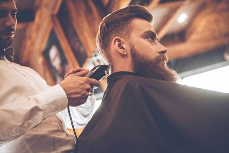 electric razor: Professional styling. Low angle view of young bearded man getting haircut by hairdresser with electric razor at barbershop