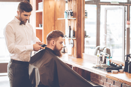 electric razor: Sharp edges. Side view of young bearded man getting haircut by hairdresser with electric razor while sitting in chair at barbershop