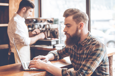 side bar: Working in cafe. Side view of young handsome bearded man using his laptop while sitting at bar counter at cafe with barista at the background