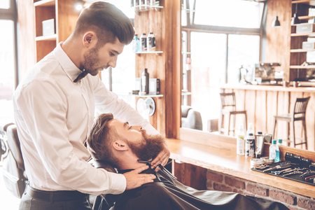 straight razor: Making his beard stylish. Side view of young bearded man getting shaved with straight edge razor by hairdresser at barbershop Stock Photo