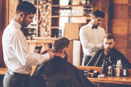 electric razor: Nape trim. Rear view of young bearded man getting haircut by hairdresser with electric razor while sitting in chair at barbershop in front of mirror Stock Photo