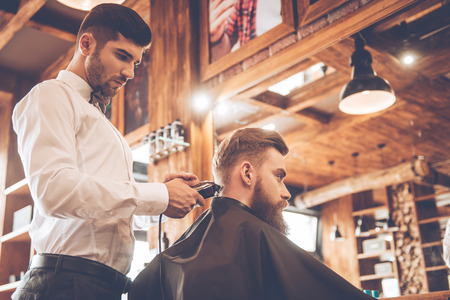 electric razor: Perfect trim at barbershop. Low angle view of young bearded man getting haircut by hairdresser with electric razor while sitting in chair at barbershop