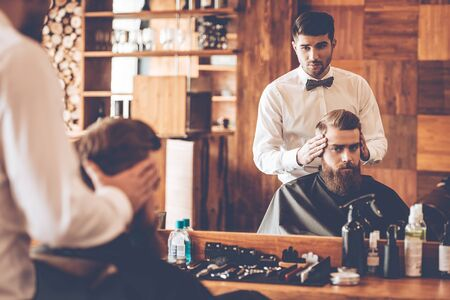 symmetry: Looking amazing. Hairdresser checking symmetry of haircut of his client in front of mirror at barbershop