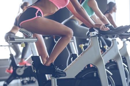 Puissance et motivation. Vue latérale partie de jeunes femmes avec des corps parfaits dans les vêtements de sport en regardant la caméra avec un sourire tout en faisant du vélo à la gym