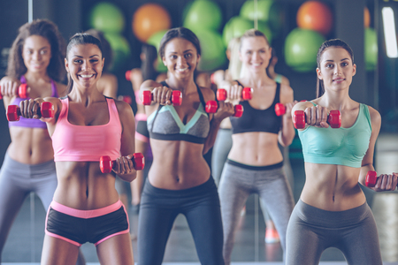 Getting fit with smile. Young beautiful women in sportswear with perfect bodies exercising with dumbbells and looking at camera with smile at gym Stock Photo - 55863341