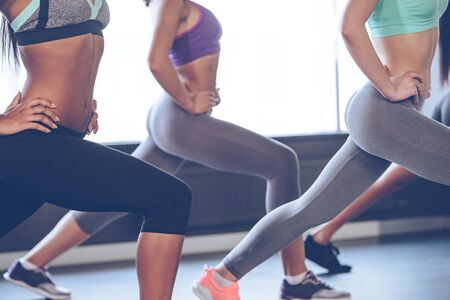built: Exercising for perfect shape. Side view part of young women with perfect buttocks in sportswear exercising while standing in front of window at gym