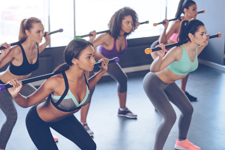 barre: Concentrated at their workout. Beautiful young women with perfect bodies in sportswear exercising with barre while standing in front of window at gym