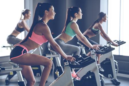 Hermoso paseo. Vista lateral de mujeres hermosas jóvenes con cuerpos perfectos en ropa deportiva mirando a otro lado con una sonrisa mientras que el ciclismo en el gimnasio Foto de archivo