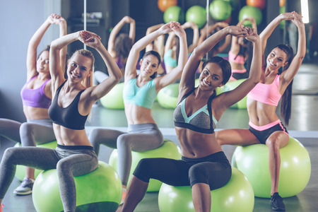 staying fit: Staying fit. Young beautiful women in sportswear with perfect bodies doing stretching and looking at camera with smile while sitting on fitness balls at gym