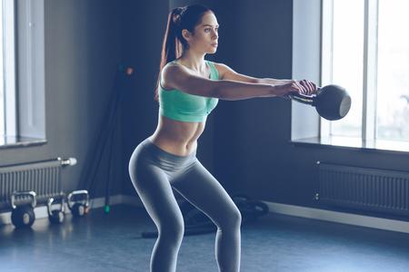 Perfekte Cross-Training. Seitenansicht der jungen schönen Frau mit perfekten Körper in der Sportkleidung arbeitet mit Kesselglocke an der Gymnastik