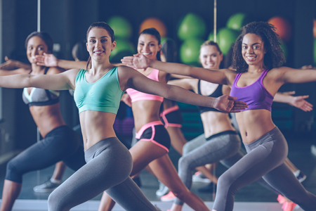staying fit: Staying fit and cheerful. Side view of beautiful young women with perfect bodies in sportswear exercising and looking at camera with smile at gym