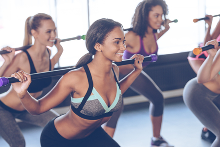 barre: One more squat. Beautiful young women with perfect bodies in sportswear exercising with barre while standing in front of window at gym