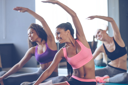 beauties: Flexible beauties. Young beautiful young women with perfect bodies in sportswear doing stretching with smile at gym