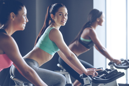 Cycling with smile. Side view of young beautiful women with perfect bodies in sportswear looking at camera with smile while cycling at gym
