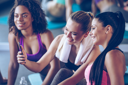 workouts: I can see progress in my workouts! Beautiful young women in sportswear discussing something with smile and using smartphone while sitting on exercise mat at gym