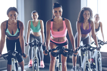 beauties: Cycling beauties. Young beautiful women with perfect bodies in sportswear looking at camera with smile while cycling at gym Stock Photo