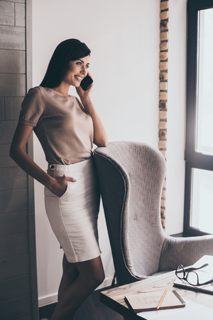 table skirt: See you tomorrow! Young beautiful cheerful woman talking on mobile phone with smile while standing at her working place Stock Photo