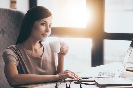 Pause café au travail. Jeune femme belle tenue tasse de café et regarder ailleurs tout en étant assis dans le fauteuil à son lieu de travail