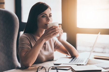 idea comfortable: Coffee brings her inspiration. Young beautiful woman drinking coffee and looking away while sitting in chair at her working place Stock Photo