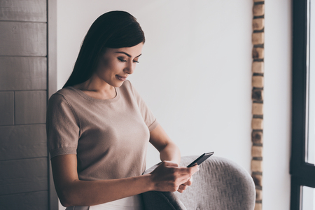 the place is important: Important message. Close-up of young beautiful woman using her smart phone with smile while standing at her working place