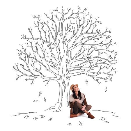 personas sentadas: Alegría del otoño. Hermosa joven alegre mirando hacia arriba con una sonrisa mientras estaba sentado bajo esbozo de árbol con las hojas que caen