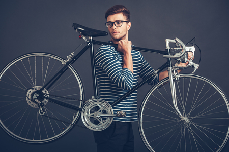 retro styled: In his own style. Confident young handsome man in glasses carrying his retro styled bicycle on shoulder and looking away while standing against grey background