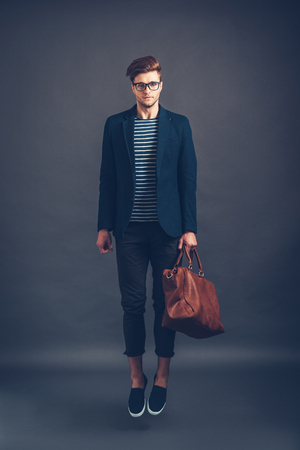 fashion style: Style in mid air. Full length of confident young handsome man in glasses carrying bag and looking at camera while jumping against grey background Stock Photo