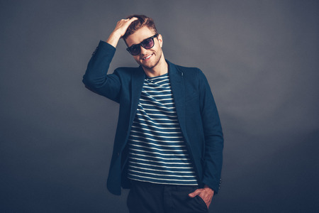 cool guy: Trendy and charming. Cheerful young handsome man in sunglasses keeping hand in hair and looking at camera with smile while standing against grey background
