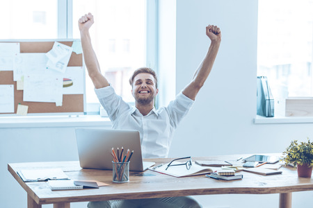 office man: This is success! Cheerful young handsome man keeping arms outstretched and keeping eyes closed with smile while sitting at his working place Stock Photo